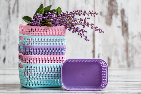 Miniature colorful plastic baskets for household use on white background Stock fotó