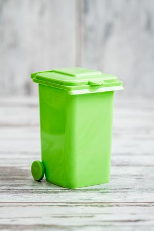 Small green plastic desk organizer box in the form of garbage container with copy space