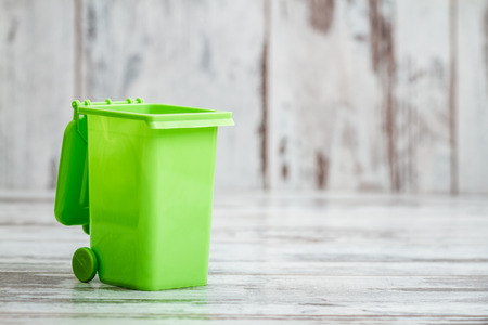 Kleine groene plastic bureau organizer vak in de vorm van vuilnis container met kopie ruimte
