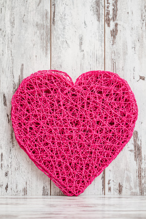 Heart shaped american style pink table mat on white wooden  background