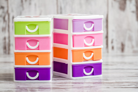 Small, cute and colorful plastic drawers on white wooden background Stockfoto