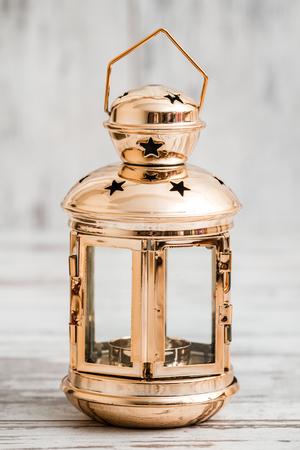 Metallic candle lantern with nostalgic look on white wooden background