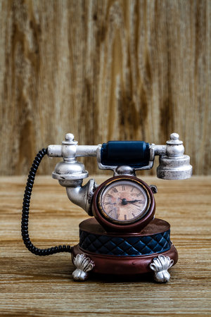 Desk clock with antic telephone shape on brown wooden background Imagens - 91901018