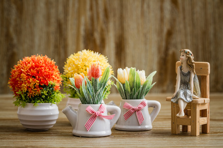 Decorative artificial flowers and angel trinket on wooden background