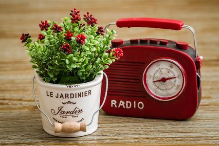 Artificial flower, red vintage radio on wooden background