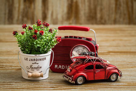 Artificial flower, vintage radio and red toy car on wooden background