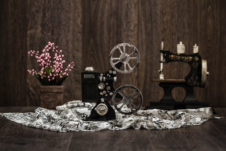 Small nostalgic decorative film camera on brown wooden background 写真素材