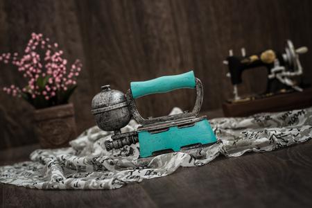 Nostalgic green iron shaped trinket on fabric Stok Fotoğraf