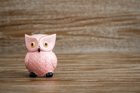 Pink owl figurine on wooden background
