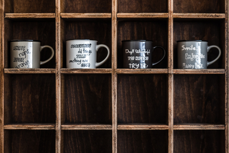 Ceramic coffee mugs on handmade wooden rustic wall shelf 免版税图像