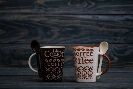 White, brown ceramic coffee mugs on wooden background