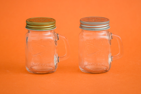 Empty salt, pepper shakers on orange background Stock Photo
