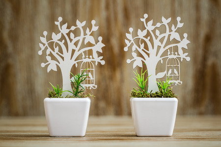 Laser cut wooden tree embellishments in white porcelain flower pots on wooden background