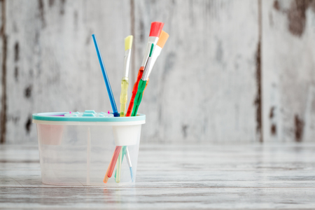 Colorful plastic brushes on white wooden background 写真素材