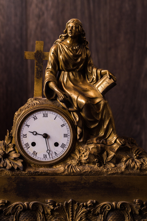 Antique brass metal figural clock on brown background