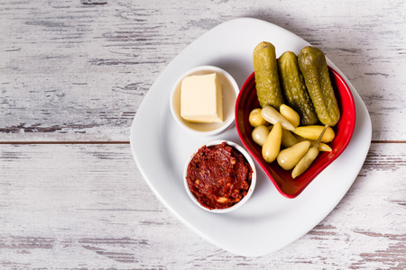 White plate with pickled cucumbers, red pepper sauce and butter