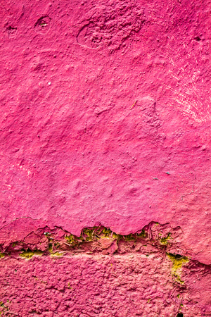 Old cracked mudbrick wall with peeled pink plaster Stock Photo