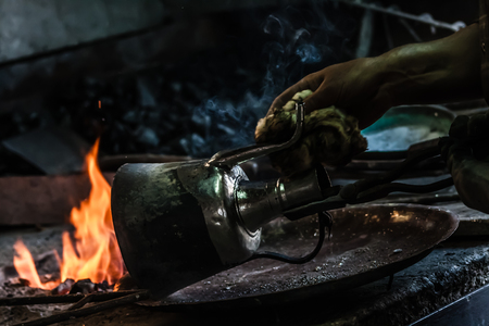 Traditional Turkish tinsmith covering the copper object with tin over fire Stok Fotoğraf