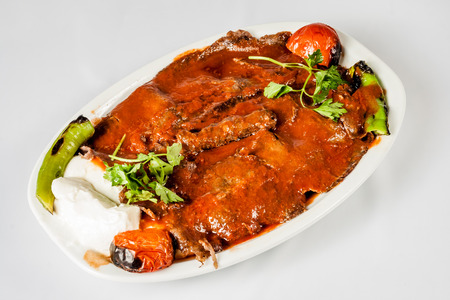 Turkish meat kebab with tomato sauce, green pepper and yoghurt Stock Photo