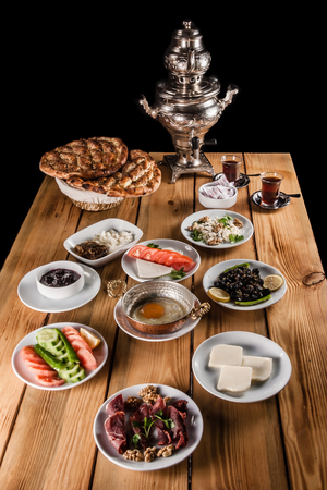Samovar and traditional Turkish breakfast table with bacon, cheese, egg, honey