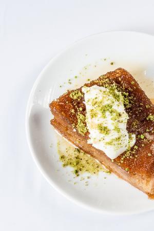 Turkish dessert ekmek kadayifi, bread pudding with cream on white