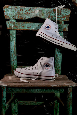ESKISEHIR, TURKEY - MAY 9, 2010: White Converse sneakers on an old green chair background