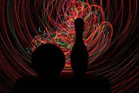 Silhouette of bowling ball and skittle in shadow of red, yellow, green, blue, black lights. Zdjęcie Seryjne
