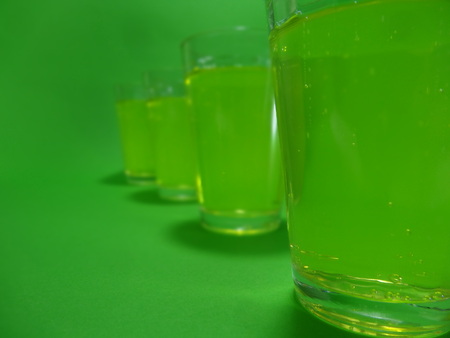 Absinthe liqueur in colored glasses on a green background