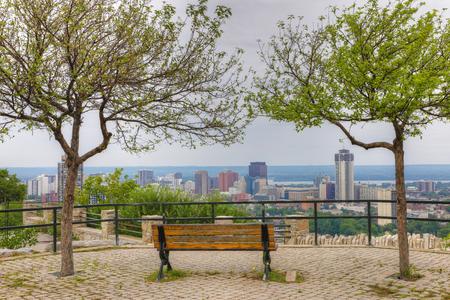 De Hamilton, Canada met parkbank op de voorgrond Stockfoto - 85310439
