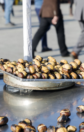 ISTANBUL - DECEMBER 27, 2015: Grilled chestnuts sellers car while people are passing by in famous Taksim Square, at the entrance of Istiklal Street, Istanbul, Turkey. Photographed with Canon EOS 5D Mark III in RAW 16bit. Stock Photo