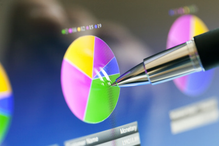 Analyzing stock market from a digital computer screen over a detailed diagram. Pointing out some details with a pen. Stock Photo