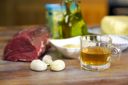 Preperation to cook a beef dish with all necessary ingredients are on a wooden table.