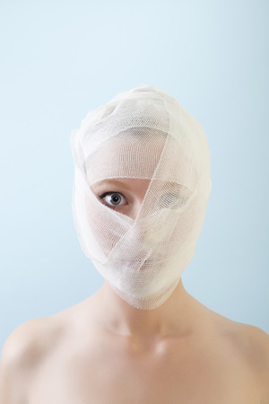 Young female is looking to the camera after her plastic surgery with bandages all over her face. Against blue background.