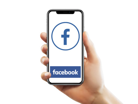 ISTANBUL - MAY 10, 2018: Apple iPhone X screen with Facebook app logo holding by a female hand against isolated white background.