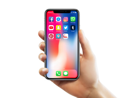 ISTANBUL - MAY 10, 2018: Apple iPhone X screen with well known social media app icons holding by a female hand against isolated white background. Editorial
