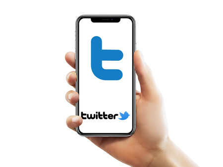 ISTANBUL - MAY 10, 2018: Apple iPhone X screen with Twitter logo holding by a female hand against isolated white background.