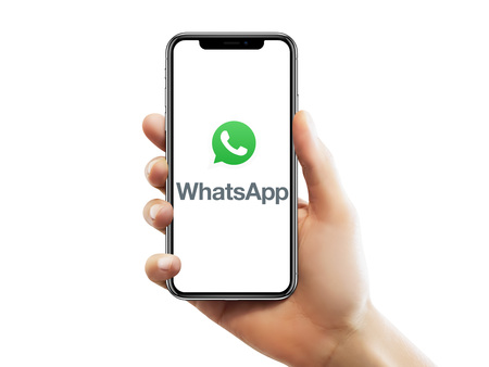 ISTANBUL - MAY 10, 2018: Apple iPhone X screen with Whatsapp logo holding by a female hand against isolated white background. Editorial