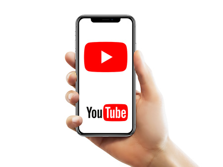 ISTANBUL - MAY 10, 2018: Apple iPhone X screen with YouTube logo holding by a female hand against isolated white background.