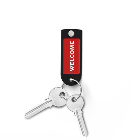 Plastic key ring with welcome tag attached on two metal keys on isolated white background. Stock Photo