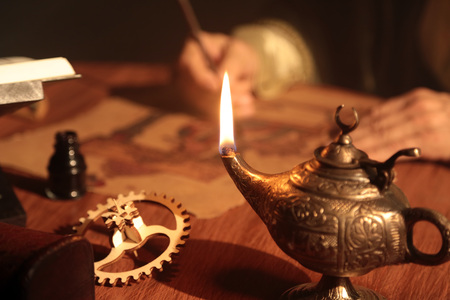 Detail shot of an old and historic Islamic scientist is working in his studio writing, reading and exploring.