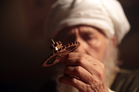 An old and historic Islamic scientist is working in his studio working on a wooden gear. Stock Photo
