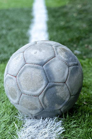 Old and used soccer ball is on field and ready to play with.