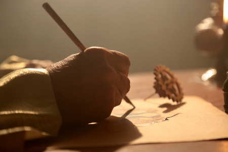 Close up shot of an old and historic Islamic scientist is working in his studio writing, reading and exploring.