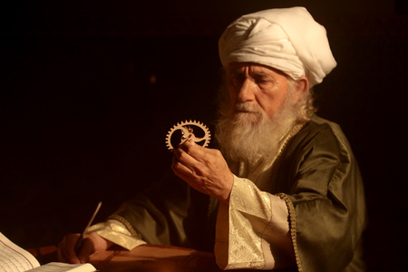 An old and historic Islamic scientist is working in his studio writing, reading and exploring.