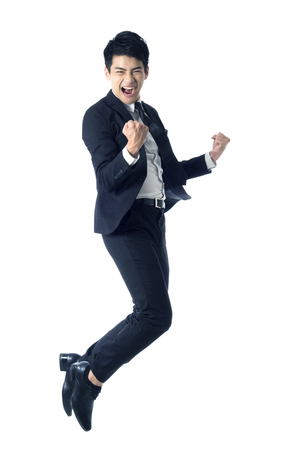 Portrait of young businessman jumping in the air and celebrating his success Stock Photo