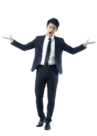 Portrait of young businessman shrugging his shoulders with furious expression Stock Photo