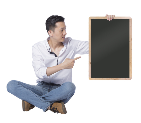 sit down: Man holding chalkboard, blank board for edited. Sit down and leg-crossed with smile on his face.