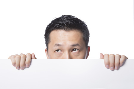 glance: man hiding behind whiteboard, stealing a glance, isolated white background, real photo Stock Photo