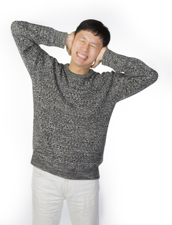 hands covering ears: Asian man suffering from headache with his hands covering ears