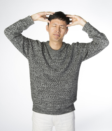 Headache asian man, tall man suffering from pain with arms up and hands on his head Banque d'images